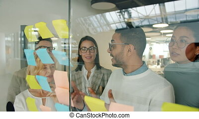 Arab man talking to colleagues discussing ideas on sticky ...