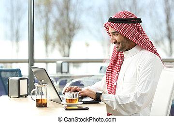 Arab saudi man working online with a laptop
