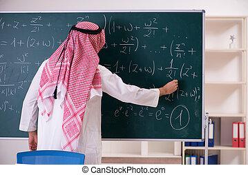 Arab teacher in front of chalkboard