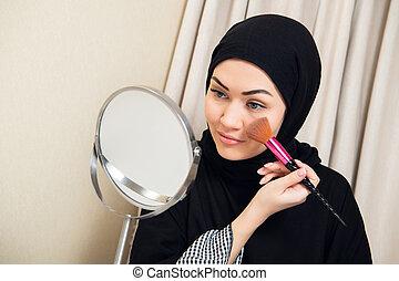 Arab woman applying makeup on her face, wearing traditional Arabian dress