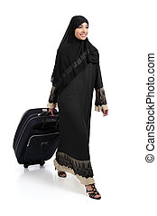 Arab woman walking carrying a suitcase