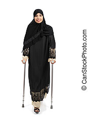 Arab woman walking with crutches isolated on a white background