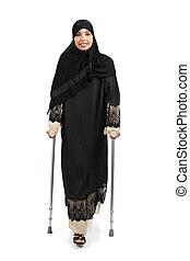Arab woman walking with crutches