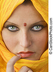 attactive and strong eyes behind an orange scarf used like a burka