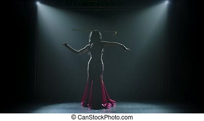 Arabian belly dancer in exotic dance holding a golden cane on his head. Shot in a dark studio with smoke and neon lighting