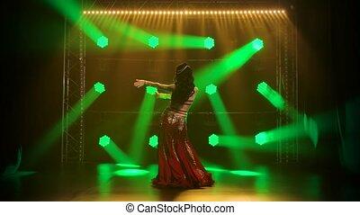 Arabian belly dancer in exotic dance. Shot in a dark studio with smoke and neon lighting