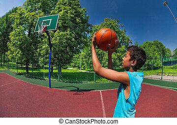 Arabian boy throwing ball in basketball goal