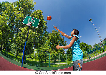 Arabian boy with ball flying to basketball goal