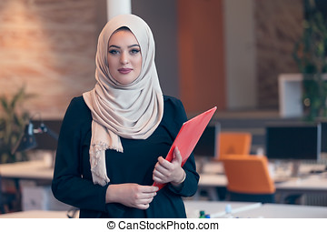 Arabian business woman holding a folder in modern startup...