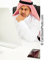 arabian businessman looking at computer screen - thoughtful...