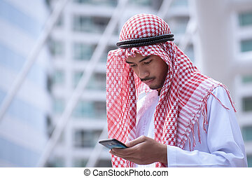 Arabian businessman using cell phone and modern business city background