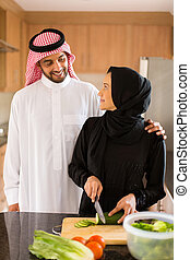 arabian couple cooking in home kitchen
