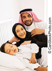 arabian couple lying on bed with their son