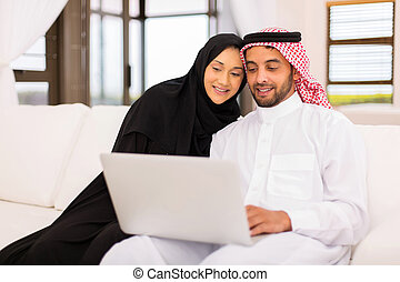 arabian couple using laptop at home
