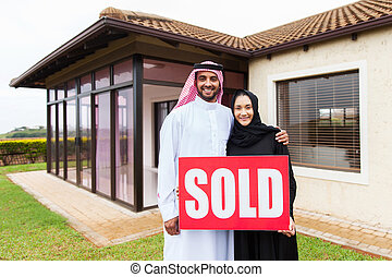 arabian couple with sold real estate sign