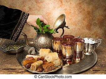 Arabian hospitality - Female hand adding mint leaves to a ...