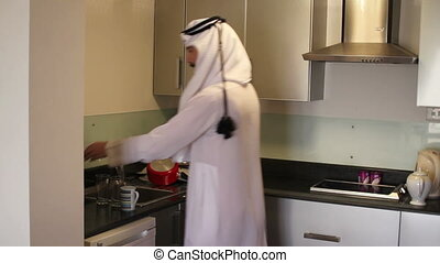 Arabian man washing dishes