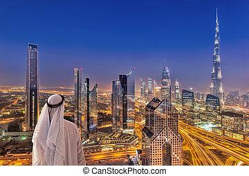 Arabian man watching night cityscape of Dubai with modern...