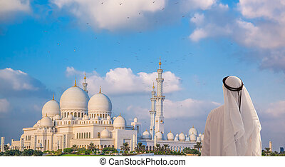 Arabian man watching Sheikh Zayed Grand Mosque in Abu-Dhabi, United Arab Emirates