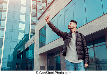 Arabian student takes selfie on smartphone outside. Happy guy looks at phone by modern building after classes