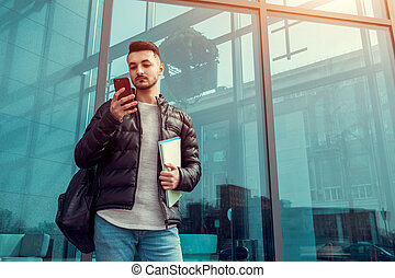 Arabian student using smartphone outside. Serious guy looks at phone in front of modern building after classes