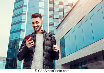 Arabian student using smartphone outside. Successful young man. Excited guy looks at phone in front of modern building
