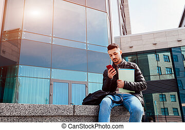 Arabian student using smartphone outside. Young guy looks at phone in front of modern building after classes