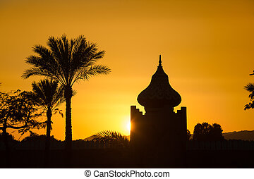 arabian orange sunset with building and palms