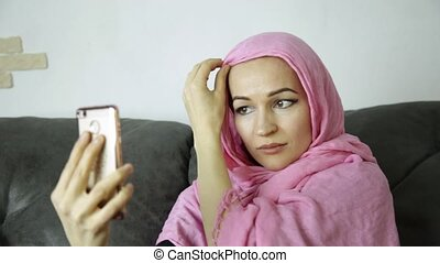 arabian woman wearing a hijab in video chat with her friends on a mobile phone