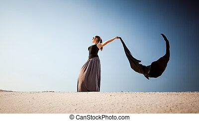 arabian woman with long cloth at desert on windy day - Photo...