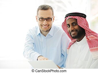 Arabic black and caucasian men working together on laptop