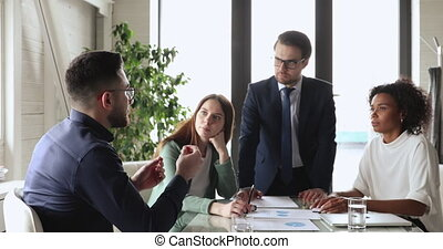 Arabic businessman mentor manager training team at group office workshop. Middle eastern executive explaining corporate project teaching diverse staff presenting strategy at boardroom briefing table.