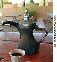 Traditional old arabic coffee pot and cup on the wooden table
