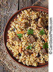 Traditional arabic cuisine national rice food called pilaf with fried lamb meat, onion, carrot and garlic spice on vintage wooden table background