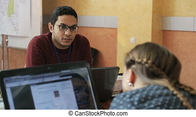 Arabic guy with stylish eyeglasses friendly talks with his colleague