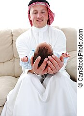 Arabic man holding a newborn baby