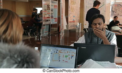 Arabic man works in office in day time with his colleagues.