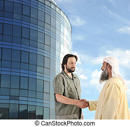 Arabic Muslim businessman meeting outdoors in front of modern building