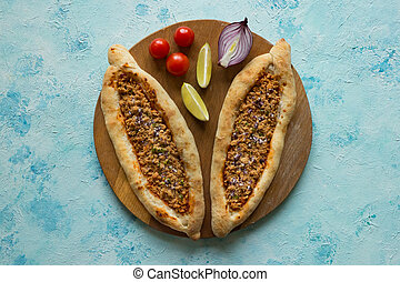 Arabic pizza Lahmacun on blue background.