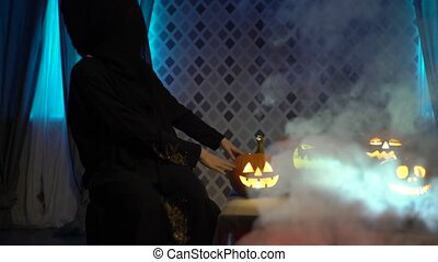Arabic woman in abaya celebrate halloween with scary funny pumpkins. Witch conjures a steaming pumpkin, casts a spell. Gates of hell with smoke and fire