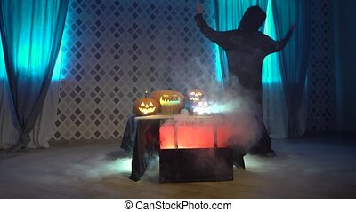 Arabic woman in abaya dances, celebrate halloween with scary funny pumpkins. Witch conjures a steaming pumpkin, casts a spell. Gates of hell with smoke and fire