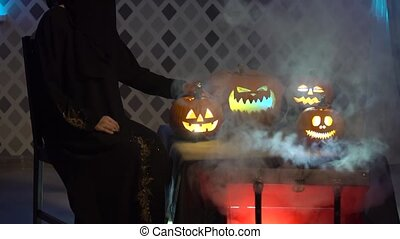 Arabic woman in abaya dances, celebrate halloween with scary funny pumpkins. Witch conjures, touches, plays with steaming pumpkin, casts a spell. Gates of hell with smoke and fire