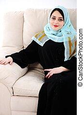 Arabic woman sitting on sofa at home