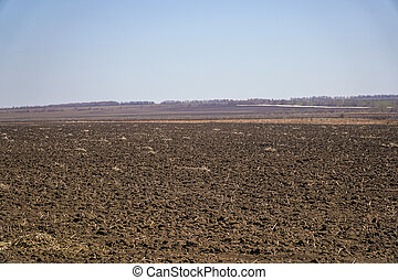 Arable land in spring against the blue sky