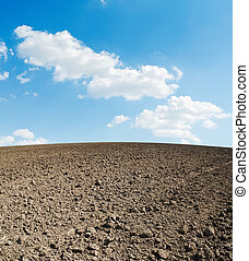 arable soil and blue sky with clouds