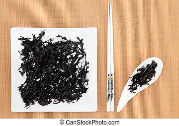 Arame Seaweed - Arame seaweed on a white plate and dish over...