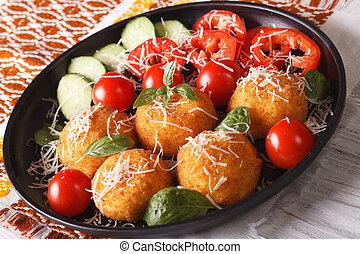 arancini rice balls with parmesan and fresh vegetables....