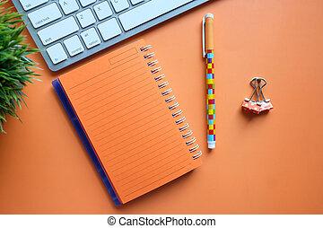 arancio colore, tastiera, blocco note, penna, scrivania