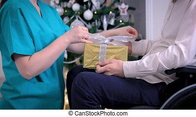 arbre, donner, homme, jeune, cadeau, fauteuil roulant, infirmière, devant, noël