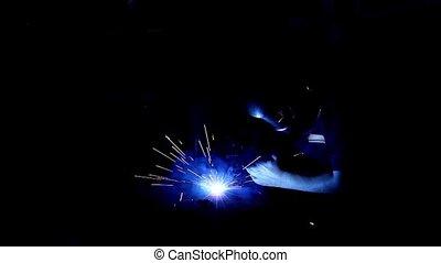 Arc welder with welding sparks.